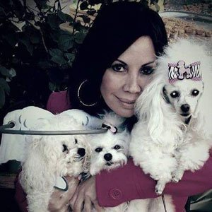 Woman holds blind pups with muffins halo as they look at the camera